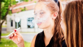 Preteen girl tries e-cigarette under the influence of her friend.