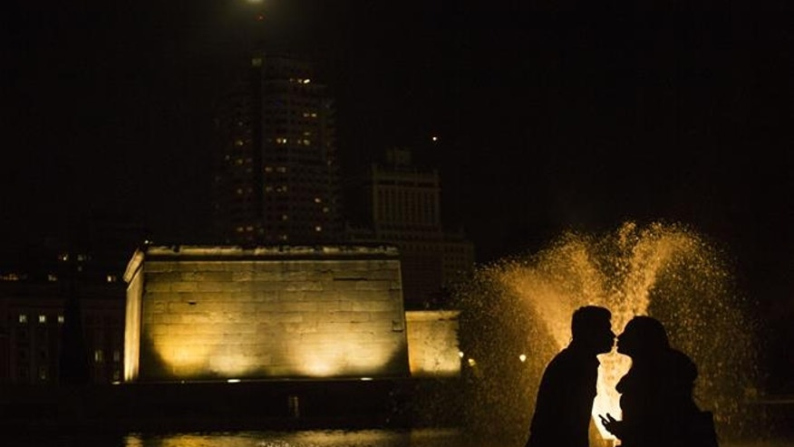 A couple kiss at the Temple of Debod as the moon shines above them in Madrid, Monday, Nov. 14, 2016.