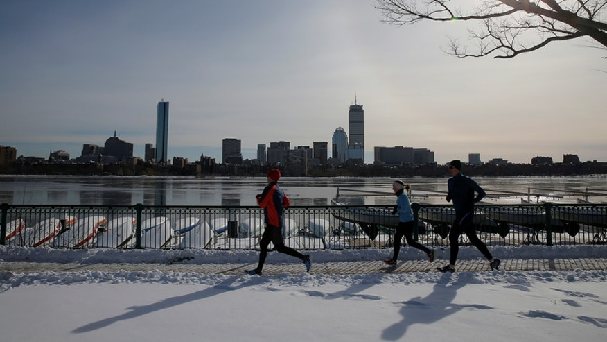 Joggers run along the Charles River past the Boston skyline on a sunny winter's day in Cambridge.