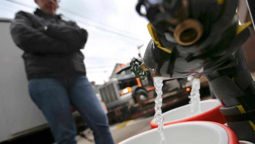 Feb. 1, 2017: Ronette Cooley watches as she fills containers with water at a city fire station in the Lawrenceville section of Pittsburgh.