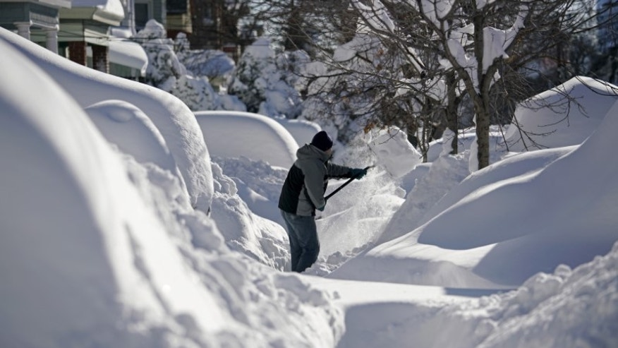 A resident shovels snow away from the entrance to his home in Union City