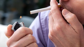 Young man lighting up a cigarette with a lighter,closeup