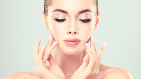 Close-up portrait of young woman with clean fresh skin. Make-up and manicure.