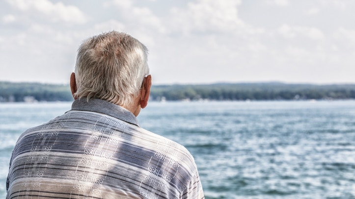 Rear view of a solitary elderly 80 plus year old senior adult man sitting at the edge of the lake watching the boats and other recreation activity on the water.