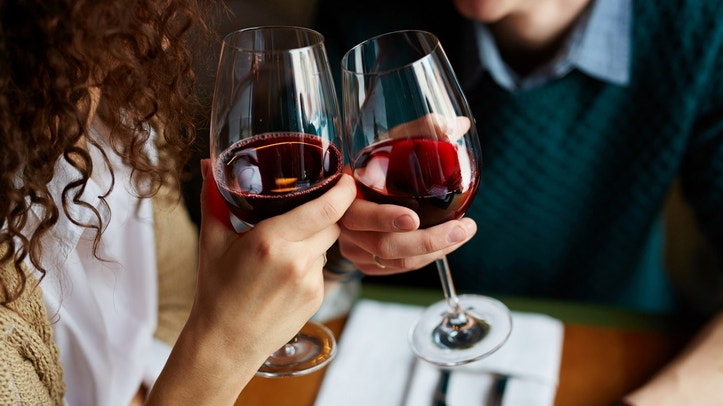 Amorous couple toasting with red wine in restaurant