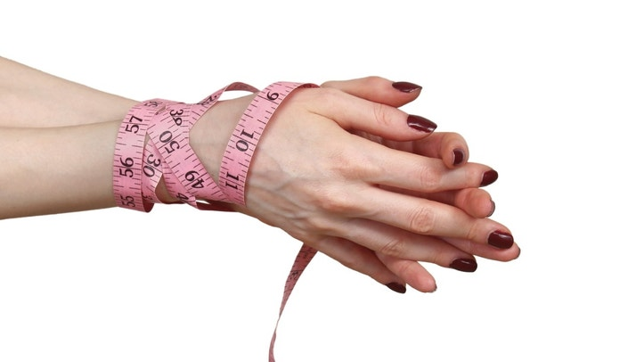Female hands tied with tape measure fighting eating disorder