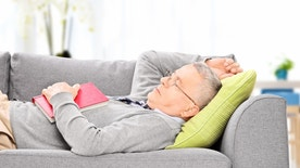 Senior man sleeping on sofa indoors