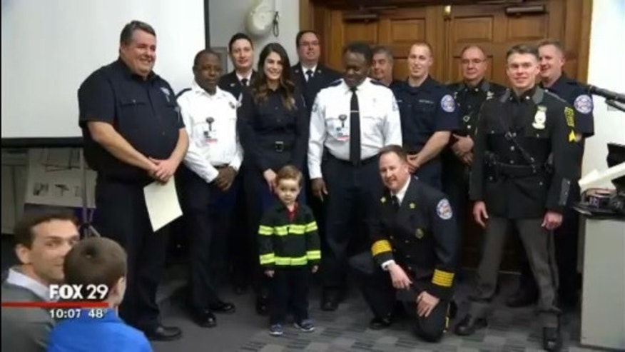 Luke McCabe is surrounded by the first responders who helped save his life in December.