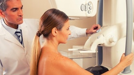 Male doctor checking mammography machine scan with patient woman in 40s.