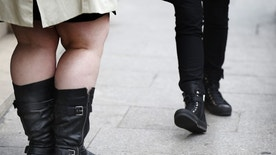 The legs of women are pictured as they walk along a street in Paris,