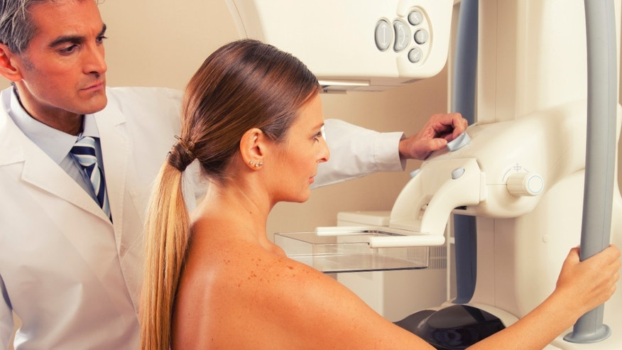 A doctor checks a mammography machine scan with an unidentified patient.