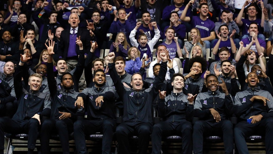 March 12, 2017: Northwestern head coach Chris Collins, center, and players react during a NCAA Division I Men's Basketball Tournament Selection Show watch party.