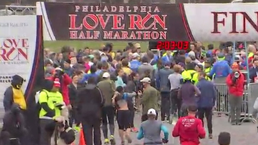 A group of runners helped an unidentified woman cross the finish line.