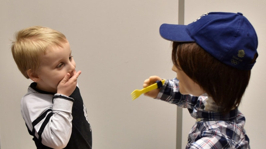 Harrison, 5, who is autistic, plays with Kaspar, a child-sized humanoid robot developed at the University of Hertfordshire.