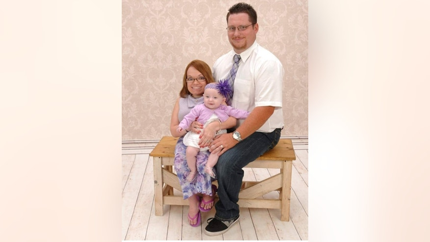 Kimberly Lord poses for a photo with her husband, Adam, and daughter Aubree, now 2.