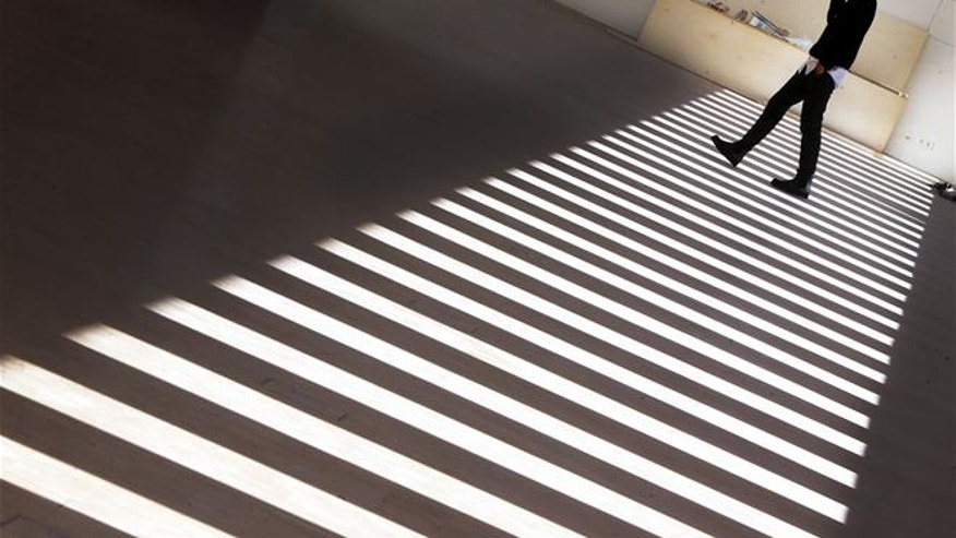 A woman walks between white stripes produces by light falling through windows of the new building of the Historical Museum in Frankfurt, Germany, Monday, Feb. 13, 2017.