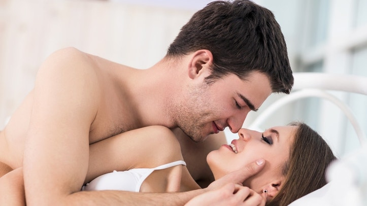 Loving couple in bed. Beautiful young loving couple lying in bed and looking to each other