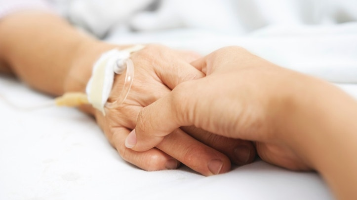 Daughter holding her mother hand, that injected with IV  in hospital