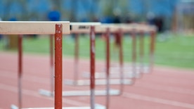 Hurdles lined up on a track, fading focus.