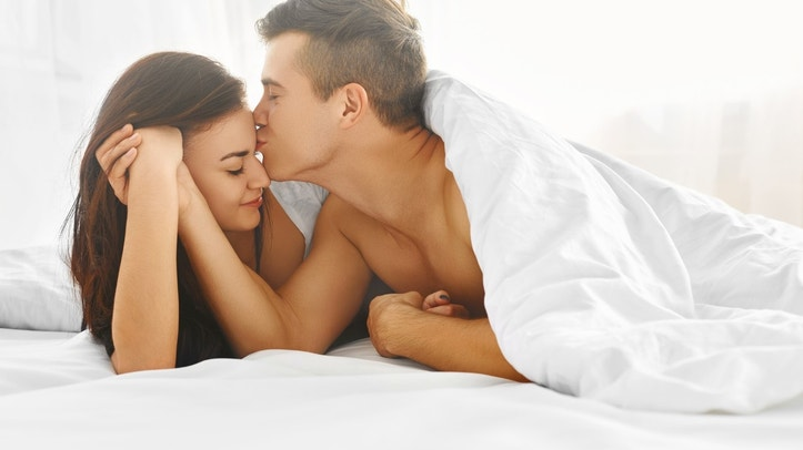 Young lovely tender couple enjoying morning lying in bed in their bedroom. Love and relationships concept.