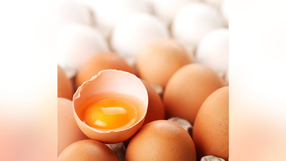 broken brown egg is among the whites of eggs.