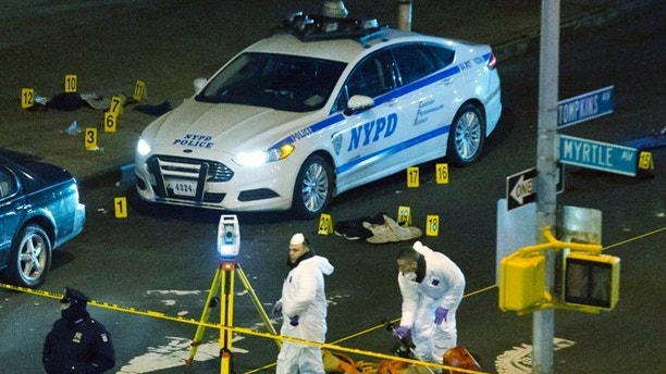 "FILE- In this Dec. 20, 2014, file photo, investigators work at the scene where two NYPD officers were shot in the Bedford-Stuyvesant neighborhood of the Brooklyn borough of New York. Wenjian Liu and Rafael Ramos, were ambushed and shot to death in their vehicle without warning by a man who approached the passenger window of their marked police car. The suspect, 28-year-old Ismaaiyl Brinsley, then fatally shot himself. In the moments leading up to the attack, Brinsley posted online he wanted to kill ""pigs"" in retaliation for the death of Eric Garner, an unarmed black man killed by police. (AP Photo/John Minchillo, File)"