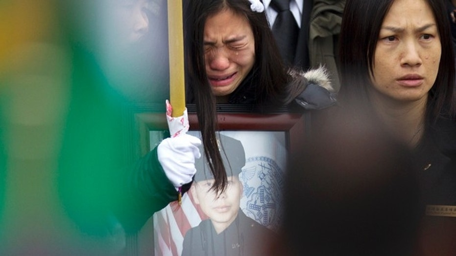 Widow Pei Xia Chen reacts while clutching a photo of slain New York Police Department officer Wenjian Liu as his casket departs his funeral in the Brooklyn borough of New York January 4, 2015.