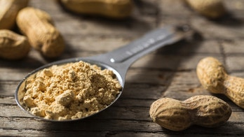 A tablespoon of dehydrated peanut powder on a rustic wood table with peanuts.