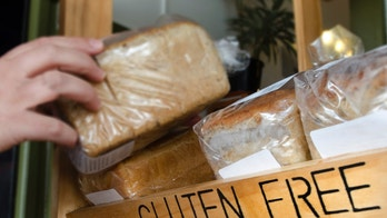 A woman hand picks up a Gluten Free loaf of bread.
