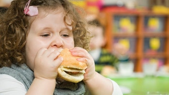 The girl is eating a hamburger.