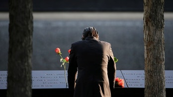 FILE--This Sept. 11, 2017, file photo shows a man standing at the edge of a waterfall pool at ground zero during a ceremony on the 16th anniversary of the 9/11 attacks in New York.  Since September 11, 2001, the neighborhood at the base of the World Trade Center has been transformed by new construction, and washed over by a wave of tourism. But this week's attack has reminded those who live, work, study and visit here of latent fears that this neighborhood would once again find itself in the crosshairs. (AP Photo/Seth Wenig, File)