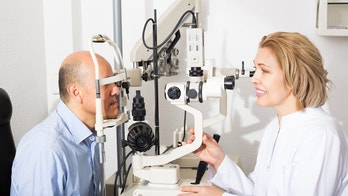Senior female optician doing eye check up to smiling man