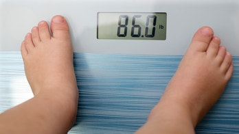 Children overweight, young boy on a bathroom scale,