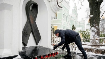 A participant lays flowers as he takes part in a ceremony to mark World AIDS Day near a monument in memory of AIDS victims in Kiev, Ukraine December 1, 2016.  REUTERS/Gleb Garanich - RC16147956E0