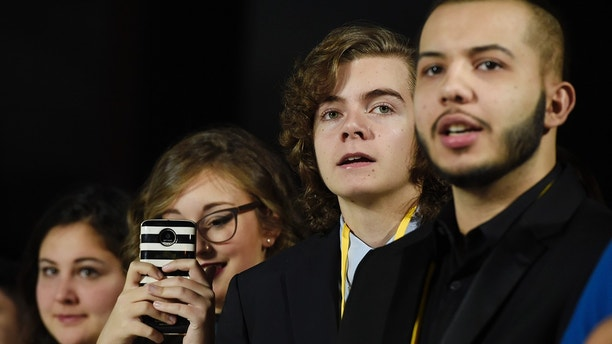 "In this Dec. 9, 2017 photo, Oliva Sava, from left, Shannon McNabb, Tyler Woodward and Chris Alegria peer down the red carpet from their spot at the premiere of the film ""Star Wars: The Last Jedi"" in Los Angeles.  The teens were among seven teens with life-threatening medical conditions who were among the special guests at the premiere as part of the Make-A-Wish Foundation. (Photo by Chris Pizzello/Invision/AP)"