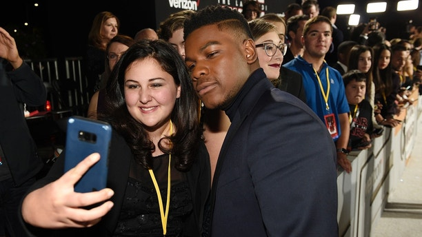 "In this Dec.  9, 2017 photo, ""Star Wars: The Last Jedi"" cast member John Boyega, right, poses for photo with Olivia Sava, 14, of New York, at the premiere of the film at the Shrine Auditorium in Los Angeles. Sava was one of seven teens with life-threatening medical conditions who were among the special guests at the premiere as part of the Make-A-Wish Foundation. (Photo by Chris Pizzello/Invision/AP)"