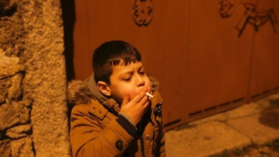 a young boy smokes in the street in the village of vale de salgueiro northern - Images Of Little Kids