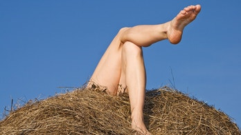 The young woman relaxing on hay in summer day