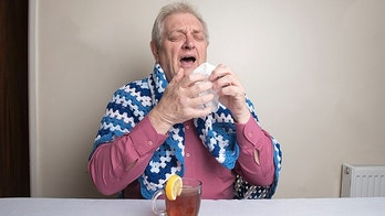 Mature man with a cold sneezing and drinking lemon and honey