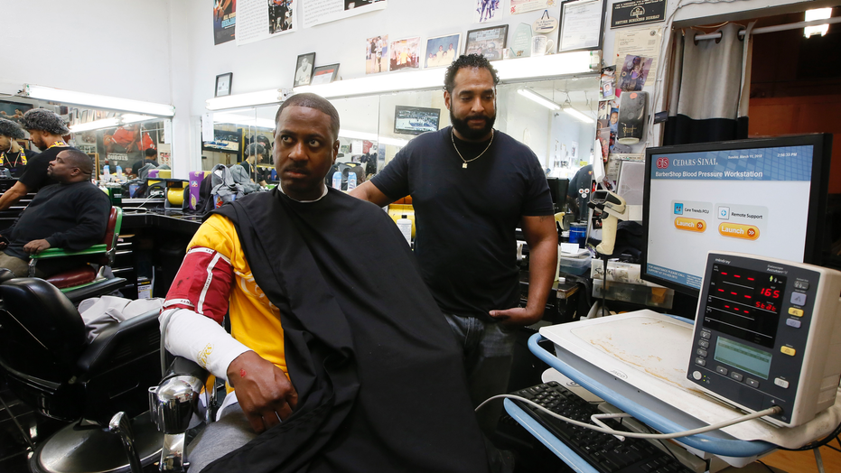 Barber Eric Muhammad, owner of A New You Barbershop measures the blood pressure of customer Marc M. Sims in Inglewood, Calif. Black male customers at dozens of Los Angeles area barbershops reduced one of their biggest health risks through a novel project that paired barbers and pharmacists to test and treat customers.
