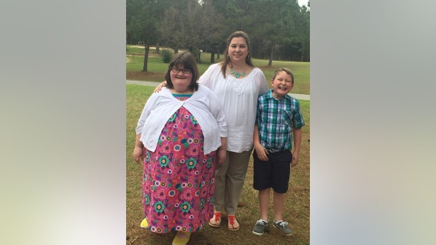 """Anna Hankins with her mother Jennifer and brother Jack. See SWNS story NYHUNGER; A 15-year-old girl who weighs 380 pounds due to a rare disease that makes her so hungry by BINS looking for Grub Anna Hankins has the Prader-Willi Syndrome, an incurable genetic disorder that results in low muscle tone, short stature The ninth grader was born prematurely and underweight, but as an infant, an insatiable appetite developed and was diagnosed with the condition of age two. She would pluck food from her parents' plates, eat a whole pack of cookies in one go, and even dig through the garbage in search of the mate. It became so extreme that her parents started locking the REFRIGERATOR and cabinets to stop Anna Ra from driving her away. The teenager from Louisville, Mississippi, now has a diet of 900 calories a day, but because her body does not break down food properly, she can not lose weight. She needs oxygen to help her breathe and she can not buckle up because of her size. Her mother, Bank Store Manager Jennifer Hankins, 37, said strangers stare and ask children why she is """"fat"""". Despite her health problems, the brave teenager loves to be the center of attention and was recently crowned queen in a pageant to celebrate women and girls with disabilities. Precious photos show Anna grinning as she is crowned Mississippi champion, and she will represent her state at Miss Awesome in Chicago in August."""