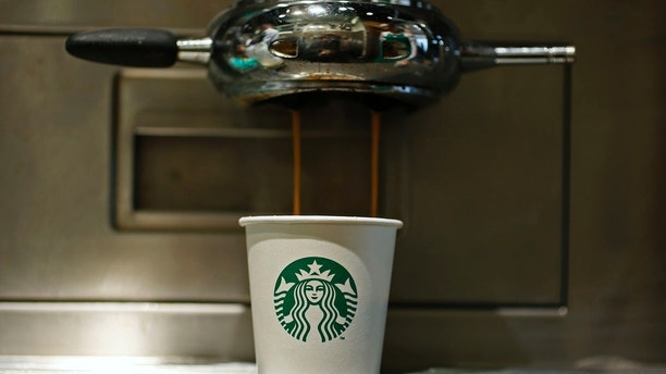 A paper cup is seen in Starbucks' Vigo Street branch in Mayfair, central London January 11, 2013.  REUTERS/Stefan Wermuth (BRITAIN - Tags: BUSINESS LOGO FOOD) - LM1E91B1ILX01