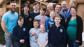 In this Friday, Feb. 16, 2018 photo, the Schwandt family poses for a portrait in front of their home in Grand Rapids, Mich. The only member not pictured is Brandon, 18. The Schwandt family has 13 sons and have welcomed a 14th into the family. The couple's latest addition was born Wednesday evening, April 18 five days before the baby's expected due date. (Casey Sykes /The Grand Rapids Press via AP)