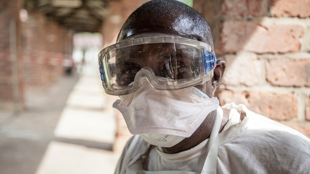 In this photo taken Saturday, May 12, 2018, a health worker wears protective clothing outside an isolation ward to diagnose and treat suspected Ebola patients, at Bikoro Hospital in Bikoro, the rural area where the Ebola outbreak was announced last week, in Congo. Congo's latest Ebola outbreak has now spread to Mbandaka, a city of more than 1 million people, a worrying shift as the deadly virus risks traveling more easily in densely populated areas. (Mark Naftalin/UNICEF via AP)