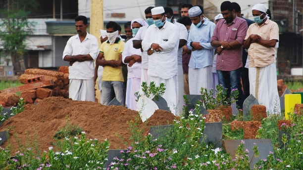 In this Thursday, May 24, 2018, photo, relatives and friends wear masks as a precautionary measure against the Nipah virus as they pray after the burial of Valachekutti Mosa's body, died of the same virus, in Kozhikode, in the southern Indian state of Kerala. More than 10 people have died of Nipah since an outbreak began earlier this month in Kerala, health officials say. There is no vaccine for the virus, which can cause raging fevers, convulsions and vomiting, and kills up to 75 percent of people who come down with it. ((AP Photo/K.Shijith)