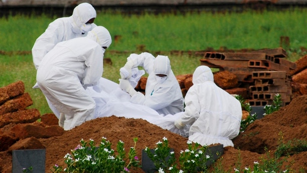 In this Thursday, May 24, 2018, photo, paramedics wear protective suits as a precautionary measure against the Nipah virus as they bury Valachekutti Mosa's body, died of the same virus, in Kozhikode, in the southern Indian state of Kerala. More than10 people have died of Nipah since an outbreak began earlier this month in Kerala, health officials say. There is no vaccine for the virus, which can cause raging fevers, convulsions and vomiting, and kills up to 75 percent of people who come down with it. (AP Photo/K.Shijith)