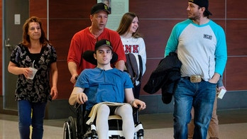 Humboldt Broncos hockey player Ryan Straschnitzki, who was paralyzed following a bus crash that killed 16 people, is wheeled by his father Tom as his mother Michelle, left, walks beside in Calgary, Alta., Wednesday, April 25, 2018. (Jeff McIntosh/The Canadian Press via AP)