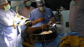 This is the moment a musician serenaded surgeons while they burned out parts of his BRAIN - so he could play guitar. See SWNS story SWGUITAR; Taskin Ibna Ali, 31, suffered from with focal hand dystonia - a rare condition also known as 'musician's cramp' which meant he lost 80% of the precise dexterity in his left hand. There is no known cure, but experts reckon it is caused byfailing motor control systems in the brain, so Taskin asked surgeons to operate. Doctors burned away the 'misfiring' parts of the brain - and an incredible video shows Taskin playing guitar on the operating theatre so surgeons could check they'd cut off the correct bit. The talented musician from Bangladesh instantly regained near-full use of his fingers for the first time in five years.