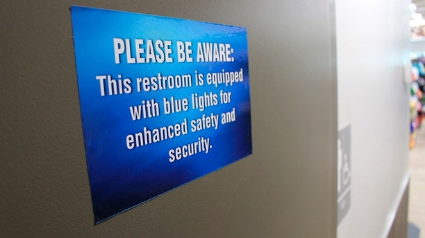 In this June 22, 2018 photo, a sign outside a public bathroom hangs at this Turkey Hill convenience store in Wilkes-Barre, Pa. The chain has installed blue light bulbs in some of its stores in hopes of discouraging drug use by making it harder for people to see their veins. (AP Photo/Michael Rubinkam)