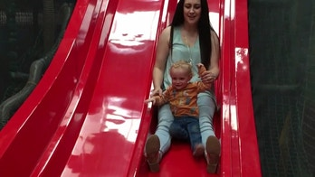 This is the horror moment a toddler's leg snapped while his mum took him down a slide on her lap. See SWNS story SWSLIDE; Shona Keetley, 26, was on a family day out with partner James, 31, and their 18-month-old son George at Rand Farm Park, Lincolnshire. Squeezing in one last ride before heading home, Shona decided to take George down the indoor slide while James filmed. Holding hands the pair set off down the slide before the tot manages to traps his foot under Shona's leg.